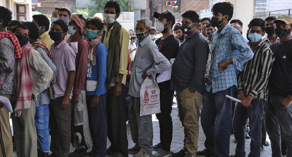People line up outside hospital in India.