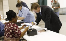 Lt. Gov. Tate Reeves signs his name onto the electronic voting log as poll worker Shirley Trigg checks his voter id in his Flowood, Miss., precinct, Tuesday, Aug. 27, 2019. Reeves is in a runoff for the Republican Party nomination for governor against former Mississippi Supreme Court Chief Justice Bill Waller Jr. (AP Photo/Rogelio V. Solis)
