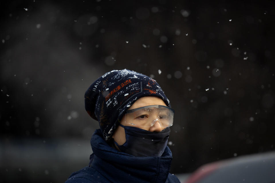 A man wearing a face mask to protect against the spread of the coronavirus waits at an intersection during a snowy morning in Beijing, Tuesday, Jan. 19, 2021. A Chinese province near Beijing grappling with a spike in coronavirus cases is reinstating tight restrictions on weddings, funerals and other family gatherings, threatening violators with criminal charges. (AP Photo/Mark Schiefelbein)