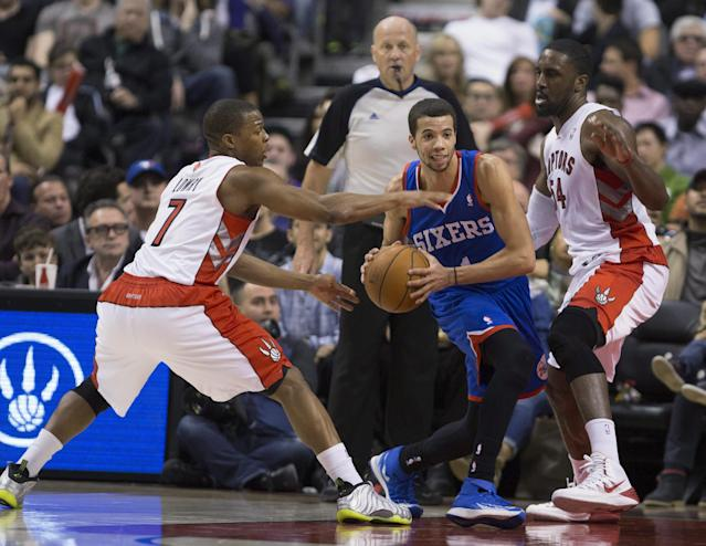 Philadelphia 76ers guard Michael Carter-Williams (1) is closely guarded by Toronto Raptors guard Kyle Lowry (7), left, and Raptors forward Patrick Patterson (54) during first half NBA action in Toronto on Wednesday, April 9, 2014. (AP Photo/The Canadian Press, Peter Power)