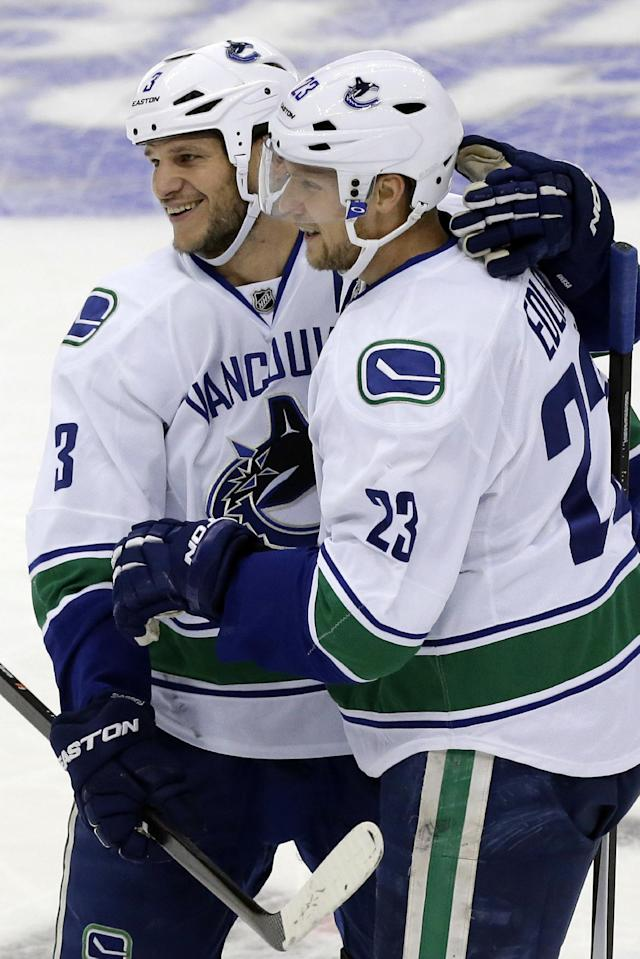 Vancouver Canucks' Alexander Edler (23) celebrates his first-period goal with teammate Kevin Bieksa (3) during an NHL hockey game against the Pittsburgh Penguins in Pittsburgh Saturday, Oct. 19, 2013.(AP Photo/Gene J. Puskar)