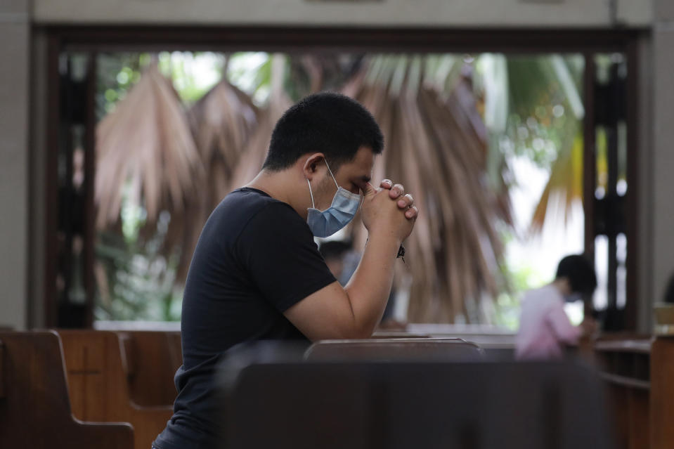 A man prays with only a few other parishioners as a measure to prevent the spread of COVID19 during Mass at the Our Lady of Consolation Parish on Sunday, Aug. 2, 2020, in Quezon city, Philippines. Coronavirus infections in the Philippines continues to surge Sunday as medical groups declared the country was waging a losing battle against the contagion and asked the president to reimpose a lockdown in the capital. (AP Photo/Aaron Favila)