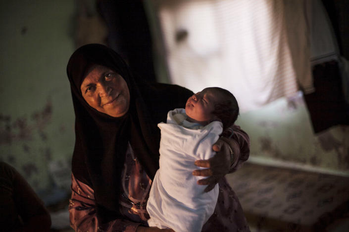 A displaced Syrian woman holds her 15-day-old granddaughter at the door of a school where almost 15 families from Homs are living in Souran village, Syria, Monday, Oct. 1, 2012. Activists say government warplanes bombed a town northwest of Aleppo, killing at least 21 people including five children. One report says 30 people were killed in the town, just four miles from the border with Turkey. (AP Photo/Manu Brabo)