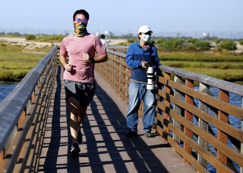 A jogger and a wildlife photographer wear masks as they enjoy the afternoon at Bolsa Chica Ecological Reserve in Huntington Beach, on Wednesday, May 20, 2020.