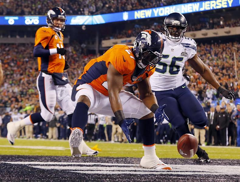 Denver Broncos' Knowshon Moreno reaches for a loose ball after the snap passed teammate Peyton Manning, left, during the first half of the NFL Super Bowl XLVIII football game Sunday, Feb. 2, 2014, in East Rutherford, N.J. Seattle Seahawks' Cliff Avril approached at right. (AP Photo/Paul Sancya)