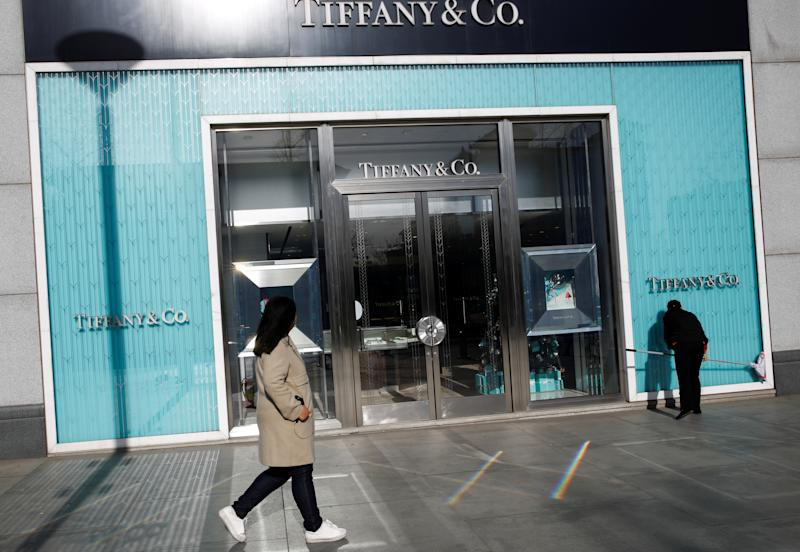 A woman cleans the windows at a Tiffany & Co. store in a luxury shopping street in Beijing, December 4, 2018. REUTERS/Thomas Peter