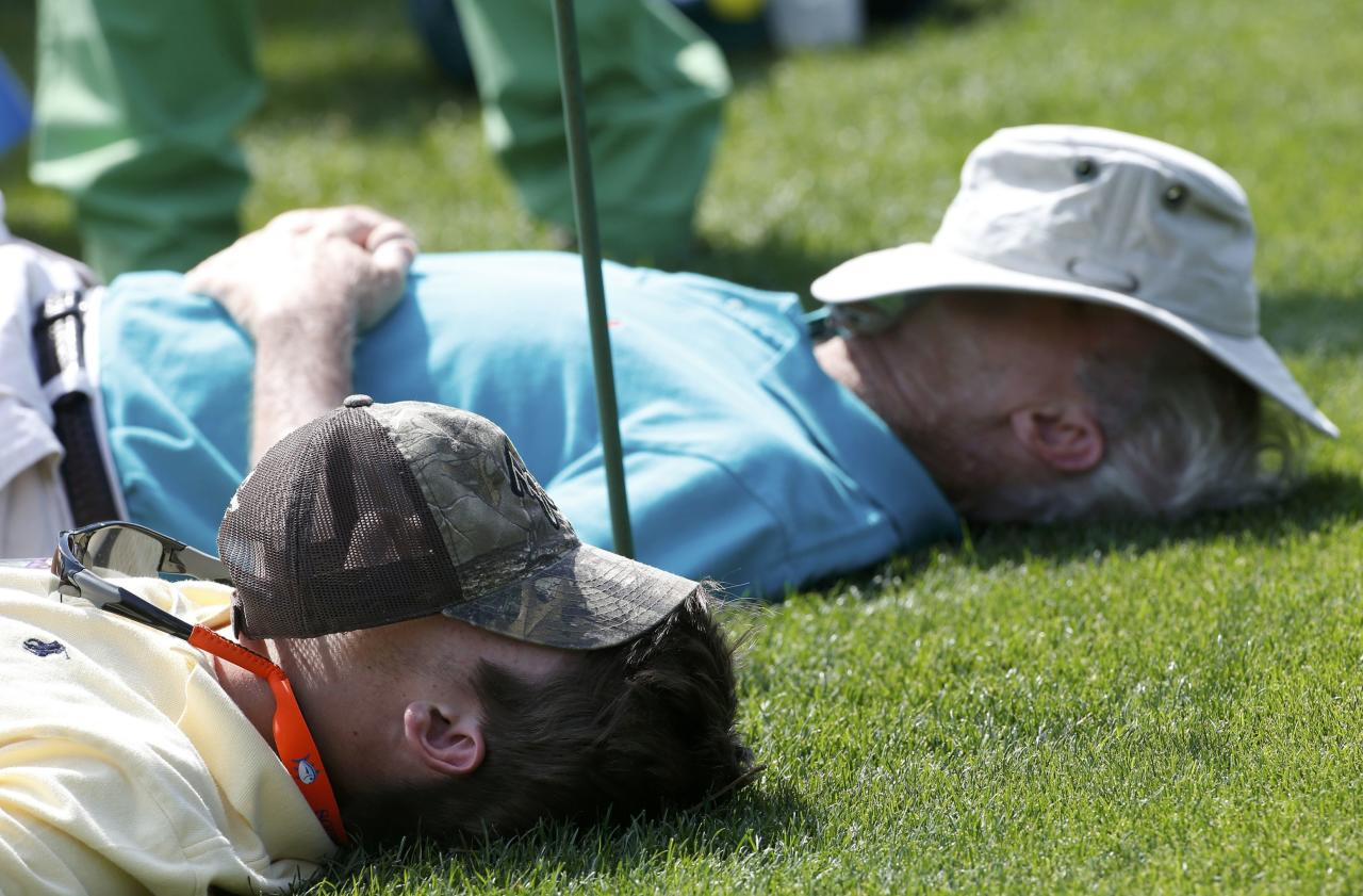 Patrons sleep on the 15th tee during the second round of the Masters golf tournament at the Augusta National Golf Club in Augusta, Georgia April 11, 2014. REUTERS/Mike Segar (UNITED STATES - Tags: SPORT GOLF)