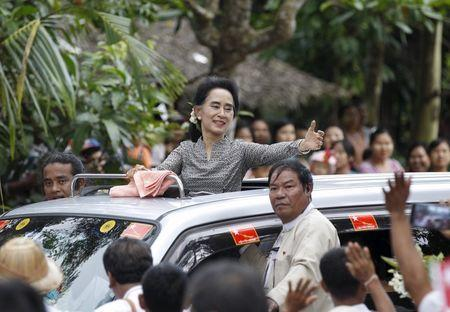 Myanmar pro-democracy leader Aung San Suu Kyi waves to supporters before giving a speech during her campaign in her constituency of Kawhmu township outside Yangon September 21, 2015. REUTERS/Soe Zeya Tun