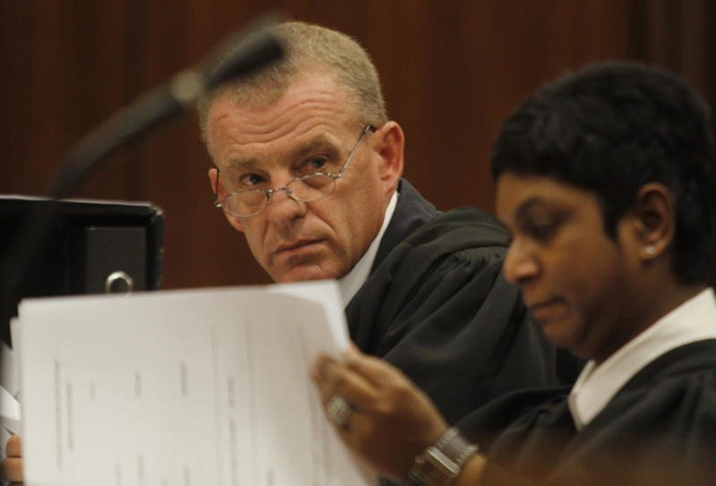 FILE In this file photo taken Thursday, March 28, 2013 state prosecutor Gerrie Nel, prepares for a hearing in the Pretoria, South Africa high court opposing the bail conditions of athlete Oscar Pistorius who is charged with the shooting death of his girlfriend Reeva Steenkamp. At the start of Pistorius' trial Monday March 3, 2014, prosecutors pressing the murder charge have listed 107 witnesses they're able to call and some will say that the world-famous athlete had a fight with Steenkamp and then intentionally killed her. (AP Photo/Denis Farrell, File)