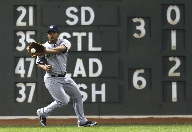 New York Yankees left fielder Alberto Gonzalez fields a single by Boston Red Sox's Dustin Pedroia during the sixth inning of a baseball game at Fenway Park, Friday, July 19, 2013, in Boston. (AP Photo/Charles Krupa)