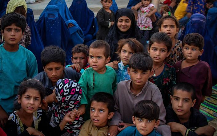 Afghan children arriving from the districts of Khan Abad, Ali Abad and Imam Sahib after fleeing from ongoing battles between the Taliban and Afghan security forces - AFP