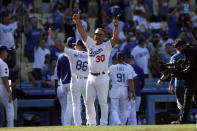 Los Angeles Dodgers manager Dave Roberts (30) salutes the fans after the Dodgers defeat the Milwaukee Brewers in a baseball game in Los Angeles, Sunday, Oct. 3, 2021. (AP Photo/Alex Gallardo)