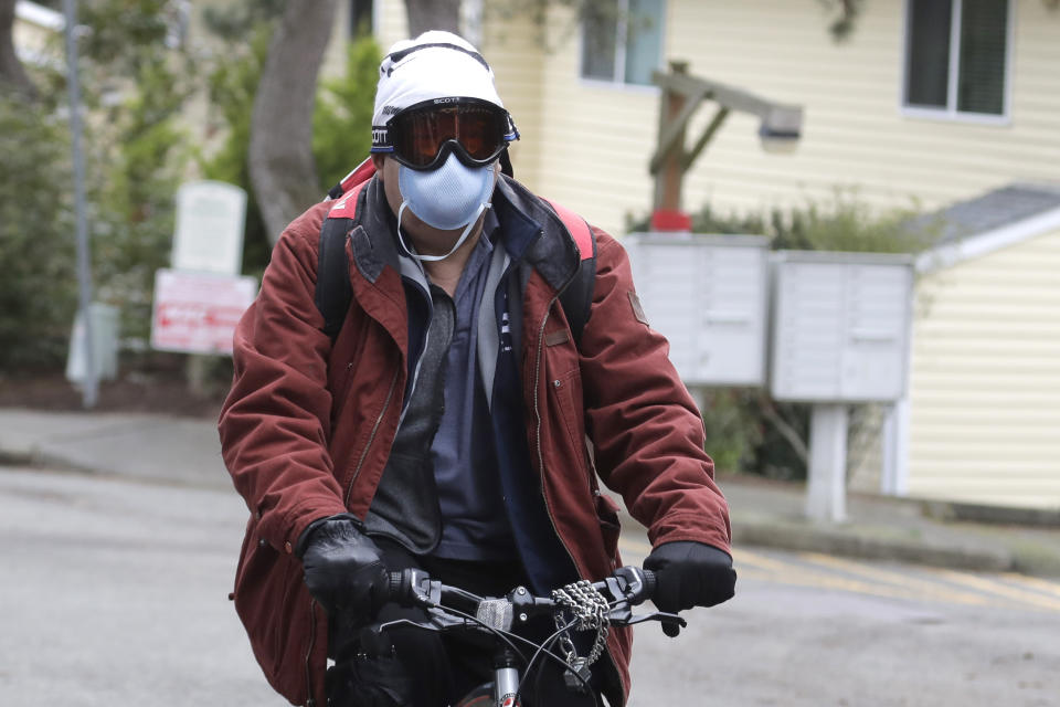 A man wearing a mask and goggles rides a bike