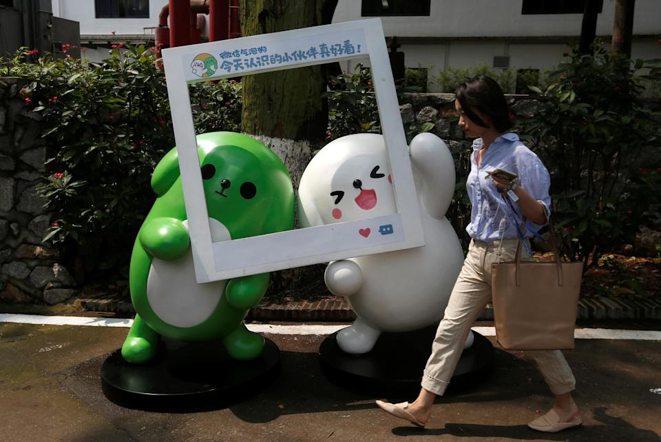 A girl walks past WeChat mascots inside TIT Creativity Industry Zone where Tencent office is located in Guangzhou, China May 9, 2017. Picture taken May 9, 2017. REUTERS/Bobby Yip