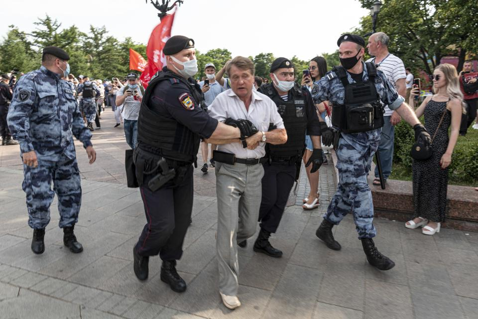 FILE - In this Saturday, June 26, 2021 file photo, police officers detain a demonstrator during an anti-vaccination protest in the center of Moscow, Russia. Faced with worrying surges of coronavirus infections driven by the more transmissible delta variant, European nations have been scrambling to ramp up vaccination drives, using a mixture of stick-and-carrot measures to persuade the reluctant to get their shots. (AP Photo/Victor Berezkin, File)