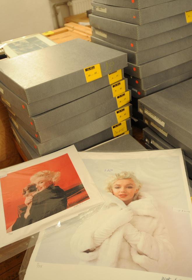 Two photos of Marylin Monroe by the late celebrity photographer Milton H. Greene are seen among boxes containing more pictures, in Warsaw, Poland, Friday, July 20, 2012. Poland plans to auction off part of a photographic collection that includes hundreds of photographs of Marilyn Monroe which ended up in Poland's possession as the result of a complex embezzlement scandal that shook the country in the early 1990s. (AP Photo/Alik Keplicz)