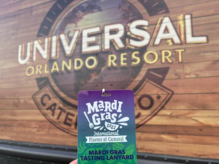 hand holding a mardi gras pass in front of a universal studios orlando sign