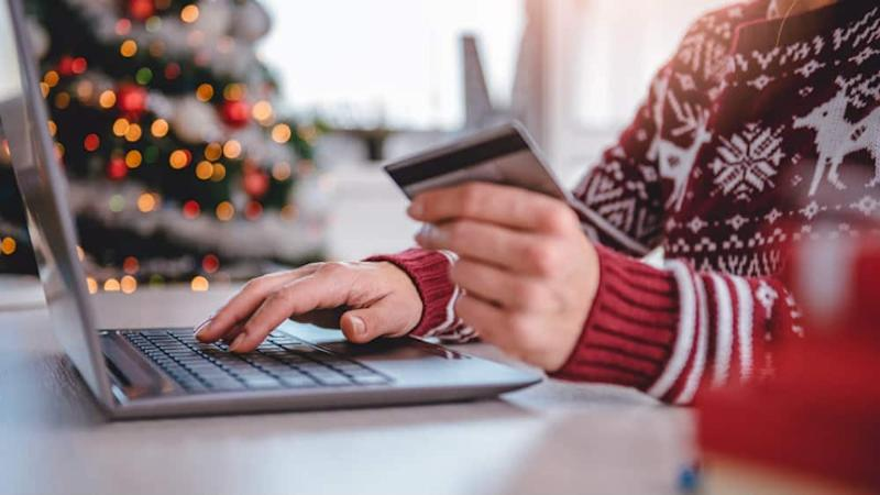 Women wearing red sweater shopping online and using credit card at home office