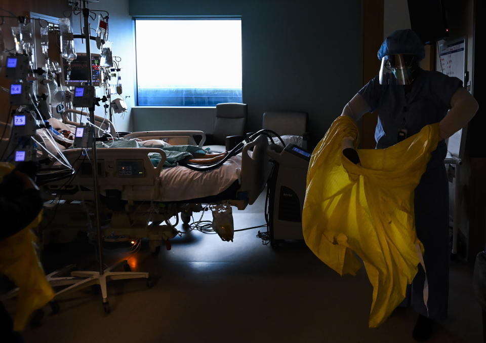 Registered nurse Jane Abas takes off her gown after tending to a COVID-19 variant patient who is intubated and on a ventilator in the intensive care unit at the Humber River Hospital in Toronto on Tuesday, April 13, 2021. (Nathan Denette/The Canadian Press via AP)
