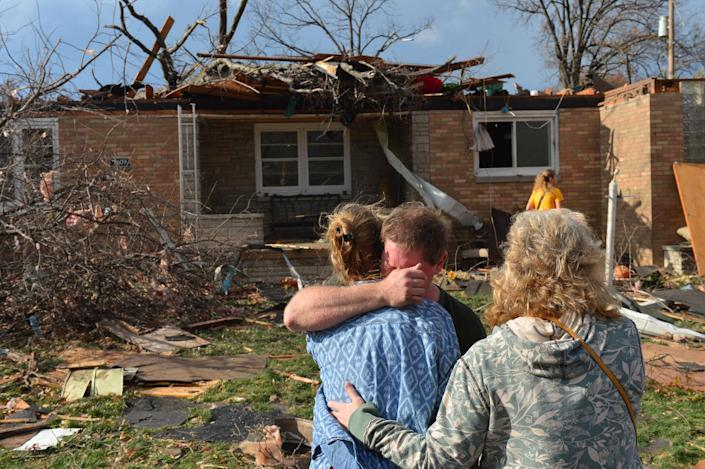 Ray Baughman embraces family shortly after his home was destroyed by a tornado that left a path of devastation through the north end of Pekin, Il., Sunday, Nov. 17, 2013. Intense thunderstorms and tornadoes swept across the Midwest on Sunday, causing extensive damage in several central Illinois communities while sending people to their basements for shelter. (AP Photo/Journal Star, Fred Zwicky) MANDATORY CREDIT