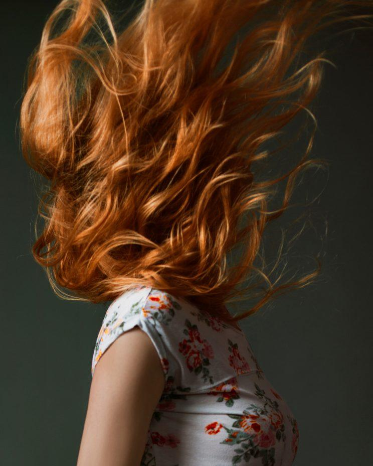 A model's face is obscured by her red hair.