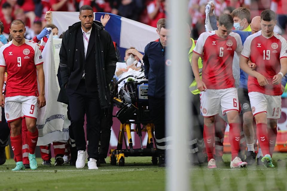 Denmark's players escort midfielder Christian Eriksen off the field after Eriksen collapsed on the pitch. (Photo by Friedemann Vogel / AFP via Getty Images)