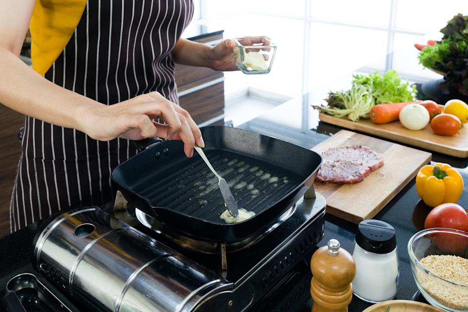 The housewife dressed in an apron putting butter in the pan prepared for frying steaks.