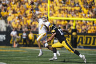 Kent State quarterback Dustin Crum (7) throws a pass over Iowa defensive end Joe Evans (13) during the first half of an NCAA college football game, Saturday, Sept. 18, 2021, in Iowa City, Iowa. (AP Photo/Charlie Neibergall)