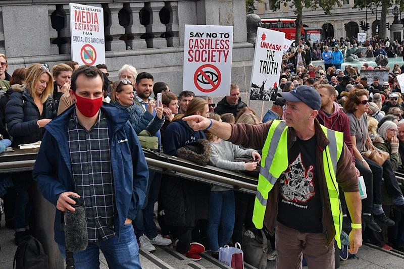 A protester (R) gestures to a member of the media (L) as he complains about the wearing of a mask, in Trafalgar Square. (Photo: JUSTIN TALLIS via Getty Images)