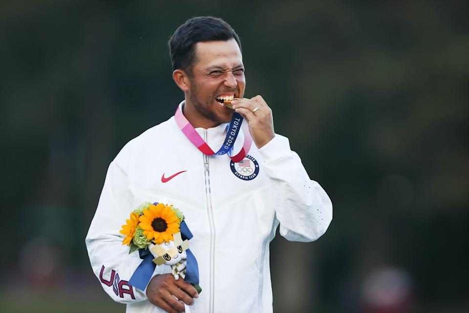 Gold medalist Xander Schauffele of the United States bites his medal during the awarding ceremony of the men's individual stroke play of golf match at Tokyo 2020 Olympics in Saitama, Japan, Aug. 1, 2021. (Photo by Zheng Huansong/Xinhua via Getty Images)