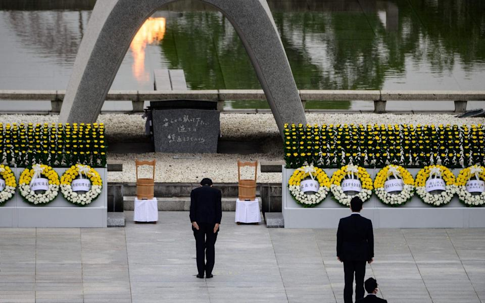 Japanese Prime Minister Shinzo Abe bows before the Memorial Cenotaph to commemorate the 75th anniversary of the Hiroshima bombing - PHILIP FONG /AFP