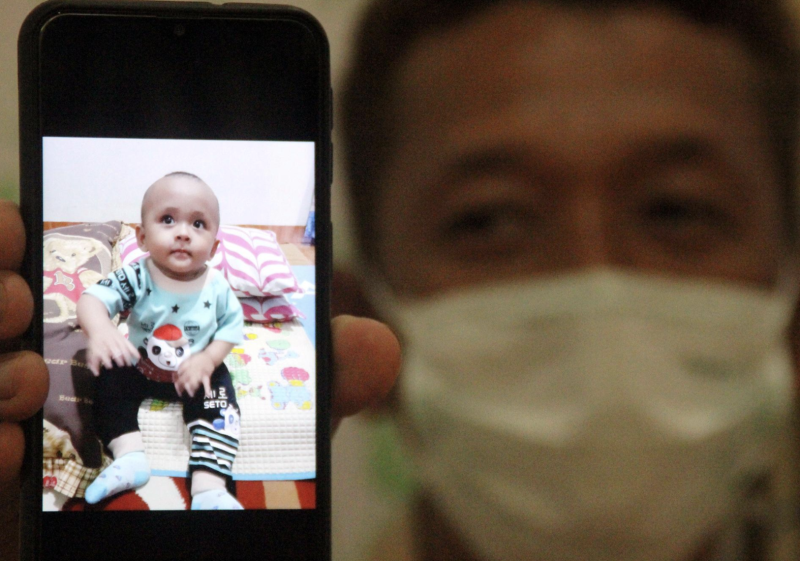 Iyansyah, 45, shows on his phone a picture of his child Fahri, who died from coronavirus. Source: Reuters