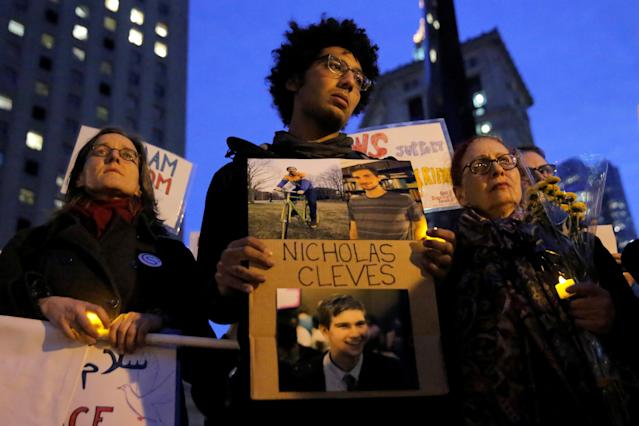 <p>Bahij Chancey (C) stands with a sign featuring his friend, New York West Side Highway pickup truck attack victim Nicholas Cleves, during a vigil in Foley Square in Manhattan, New York, Nov. 1, 2017. (Photo: Andrew Kelly/Reuters) </p>