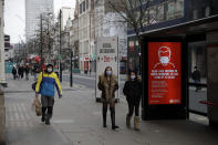 People wearing face masks to curb the spread of coronavirus walks past a social distancing sign on Oxford Street in London, Friday, Jan. 15, 2021, during England's third national lockdown since the coronavirus outbreak began. The U.K. is under an indefinite national lockdown to curb the spread of the new variant, with nonessential shops, gyms and hairdressers closed, most people working from home and schools largely offering remote learning. (AP Photo/Matt Dunham)