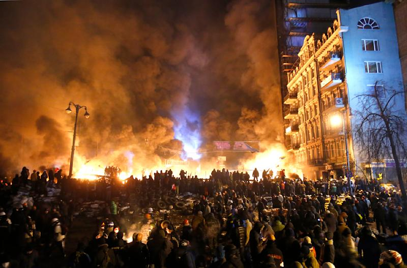 Black smoke and fireballs rise during clashes between protesters and police in central Kiev, Ukraine, early Saturday, Jan. 25, 2014. As riots spread from Ukraine's embattled capital to nearly half of the country, President Viktor Yanukovych promised Friday to reshuffle his government and make other concessions - but a top opposition leader said nothing short of his resignation would do. (AP Photo/Sergei Grits)