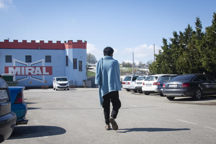 A migrant man walks outside the Miral camp, in Velika Kladusa, Bosnia, Wednesday, April 7, 2021. Bosnia is seeing a rise in coronavirus infections among migrants and refugees living in its camps, as it struggles to cope with one of the Balkans' highest COVID-19 death and infection rates among the general population.(AP Photo/Davor Midzic)
