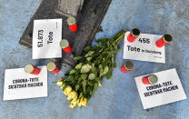 Candles and flowers to honor those who died with or of COVID-19 are set at a main shopping street in Duisburg, Germany, Monday, Jan. 25, 2021. Notes reading 'make corona deaths visible', '51.873 deaths' and '455 deaths in Duisburg'. (AP Photo/Martin Meissner)