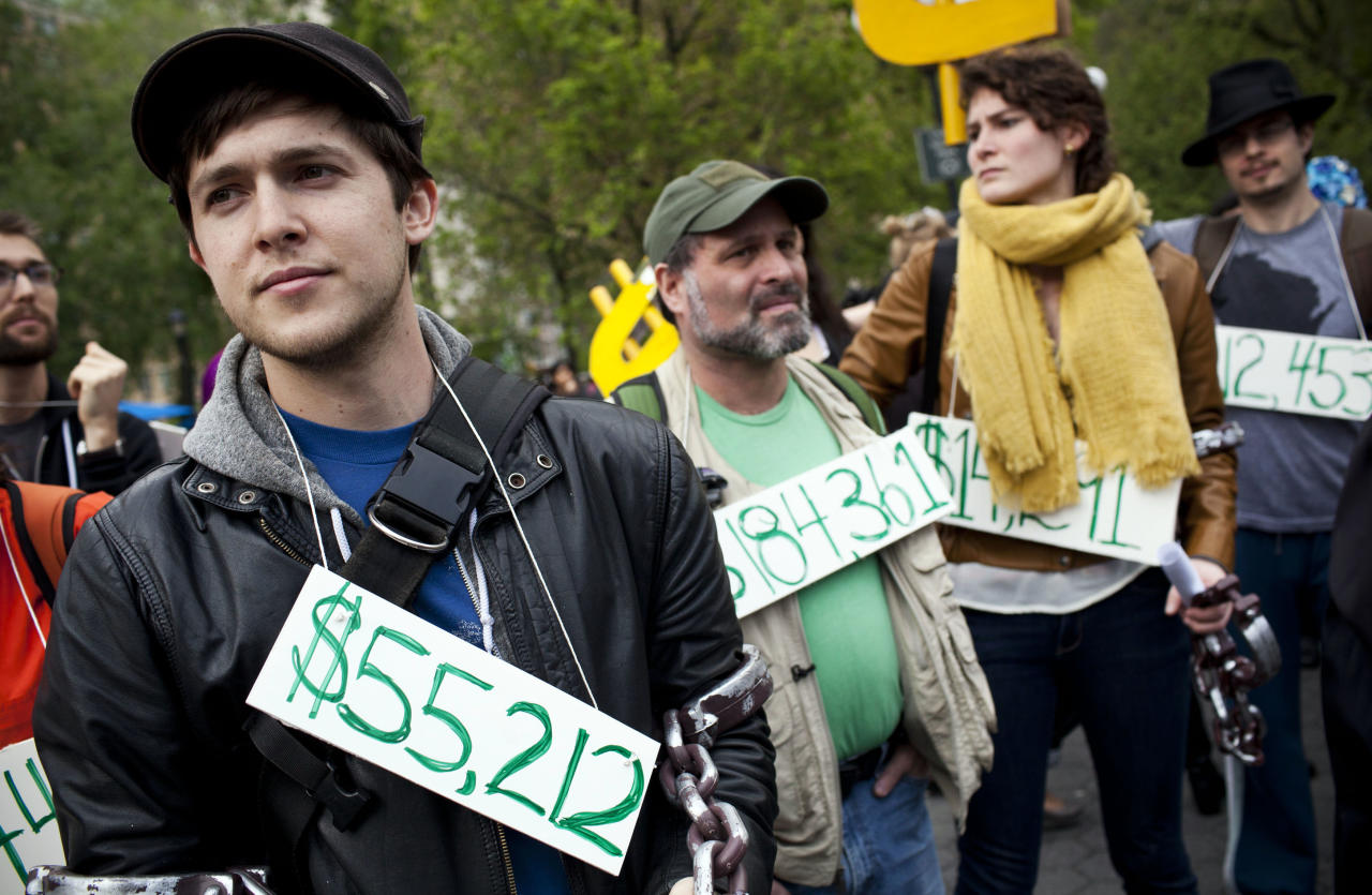 Occupy Wall Street demonstrators participating in a street-theater production wear signs around their neck representing their student debt during a protest against the rising national student debt in Union Square, in New York.