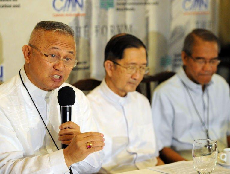 Roman Catholic archbishop Jose Palma (L) speaks during a press conference in Manila on January 29, 2013