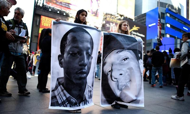 Aliya Donn (left) and Mia Robbins hold pictures of Kalief Browder (left) and Christopher Robinson, who both died as a result of alleged official misconduct related to Rikers Island prison.