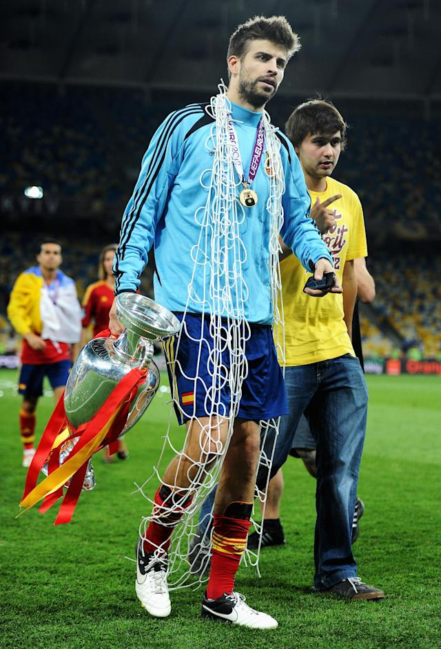 KIEV, UKRAINE - JULY 01: Gerard Pique of Spain walks across the pitch with the trophy following victory in the UEFA EURO 2012 final match between Spain and Italy at the Olympic Stadium on July 1, 2012 in Kiev, Ukraine. (Photo by Jasper Juinen/Getty Images)