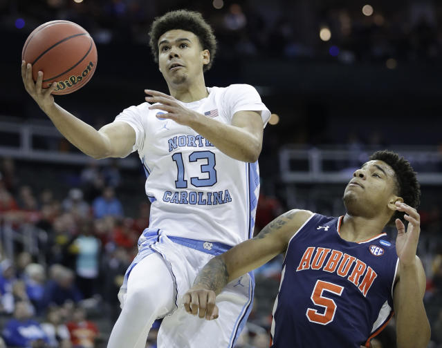 FILE - In this March 29, 2019, file photo, North Carolina's Cameron Johnson (13) heads to the basket past Auburn's Chuma Okeke (5) during the first half of a men's NCAA tournament college basketball Midwest Regional semifinal game, in Kansas City, Mo. Johnson is a first-round prospect in Thursday's NBA draft. (AP Photo/Charlie Riedel, File)