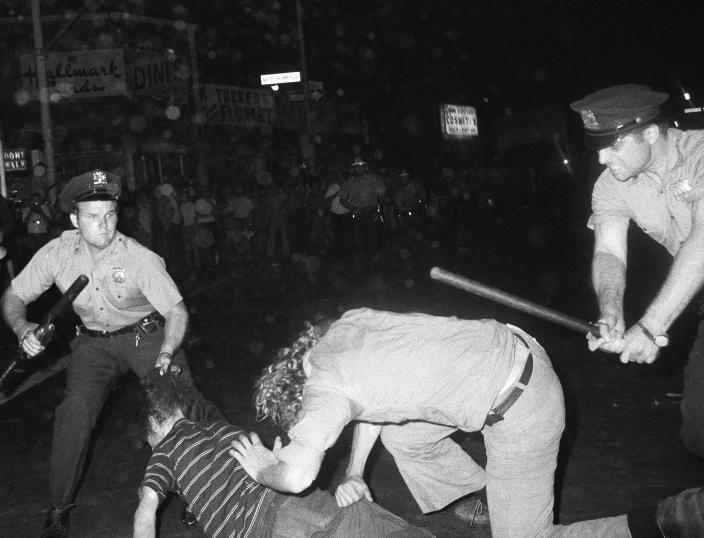 FILE- In this Aug. 31,1970 file photo, an NYPD officer grabs a youth by the hair as another officer clubs a young man during a confrontation in Greenwich Village after a Gay Power march in New York. As Pride weekend approaches, the recent decision by organizers of New York City's event to ban LGBTQ police officers from marching in future parades while wearing their uniforms has put a spotlight on issues of identity and belonging, power and marginalization.For some, cops shouldn't have a visible presence at a march that commemorates the 1969 Stonewall uprising, sparked by a police raid on a gay bar. (AP Photo/File)