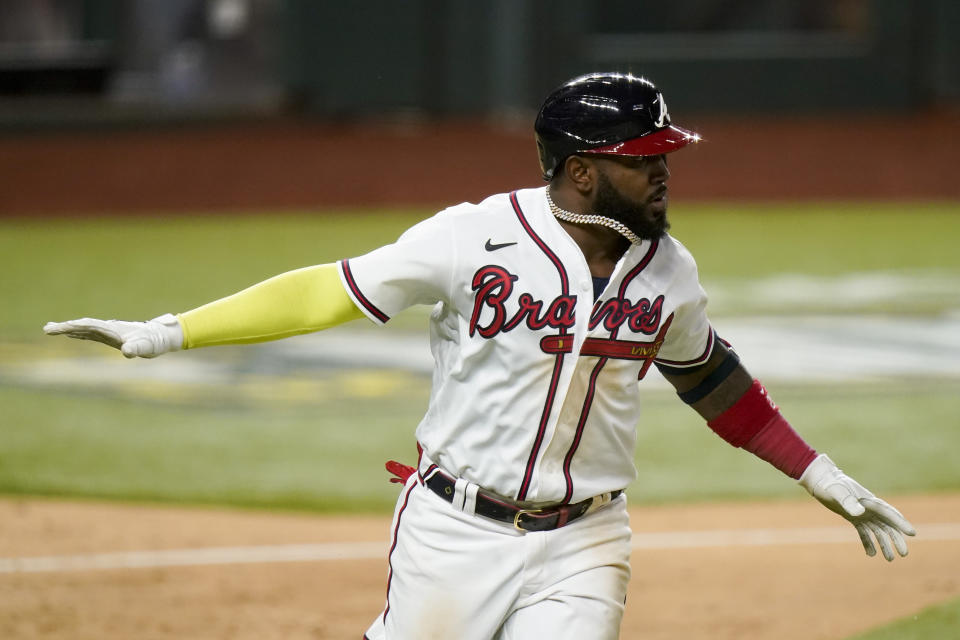 Atlanta Braves' Marcell Ozuna celebrates a RBI-single against the Los Angeles Dodgers during the eighth inning in Game 4 of a baseball National League Championship Series Thursday, Oct. 15, 2020, in Arlington, Texas. (AP Photo/Eric Gay)