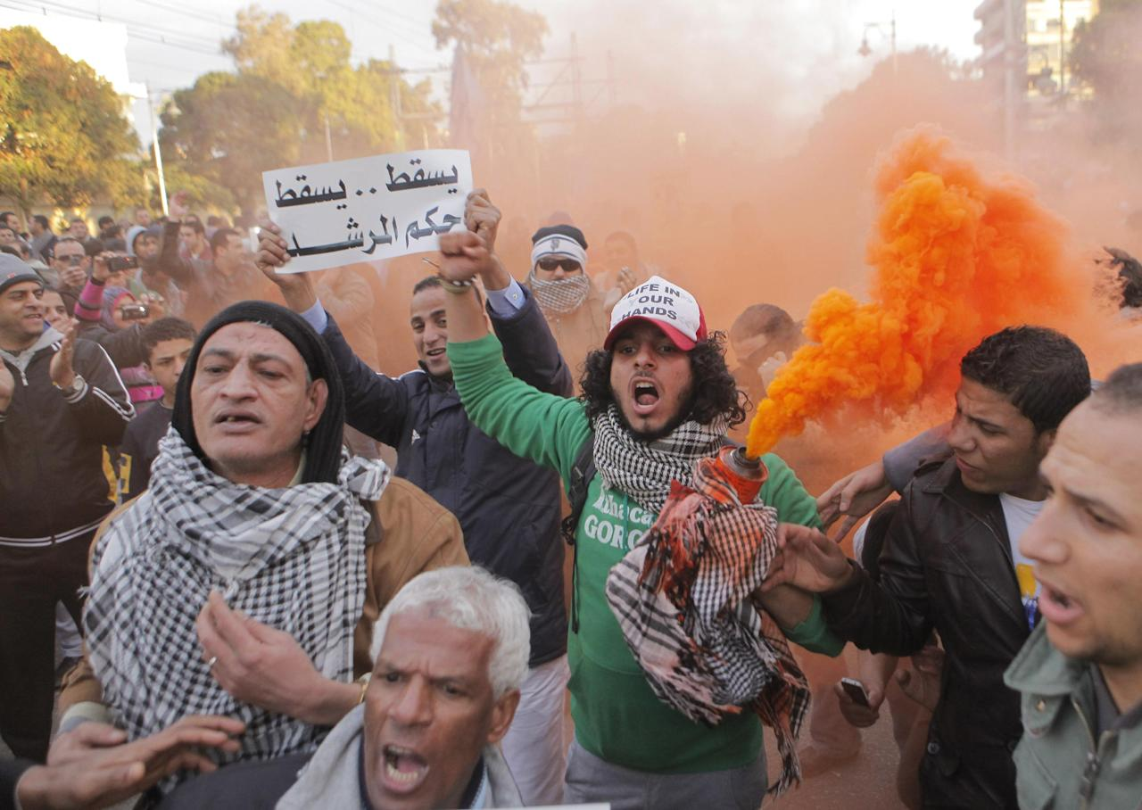 "Egyptians shout slogans during anti-President Mohammed Morsi protest in front of the presidential palace in Cairo, Egypt, Friday, Feb. 1, 2013. Thousands of Egyptians marched across the country, chanting against the rule of the Islamist President Mohammed Morsi, in a fresh wave of protests Friday, even as cracks appeared in the ranks of the opposition after its political leaders met for the first time with the rival Muslim Brotherhood. Arabic reads, ""down with brotherhood rule."" (AP Photo/Amr Nabil)"