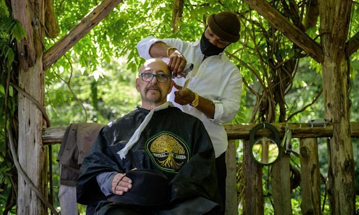 Barber Herman James cuts a clients hair under a pergola in Central Park in New York City.