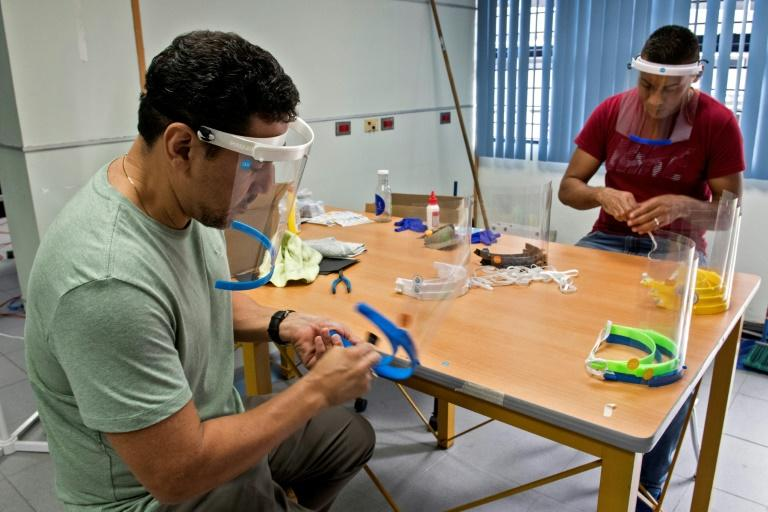 Students and professors from the University of Costa Rica engineering school are making face shields to prevent the spread of COVID-19 (AFP Photo/Ezequiel BECERRA)