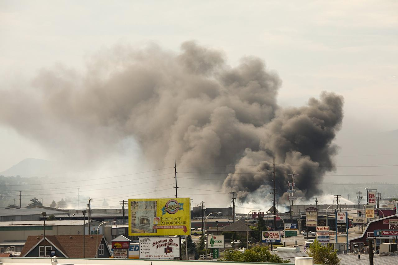 """Smoke from burning commercial buildings that were ignited by the Sleepy Hollow fire rises above Wenatchee, Washington June 29, 2015. A wildfire racing through central Washington state """"blew up"""" overnight, threatening homes and businesses as flames enveloped roughly 3,000 acres, nearly double the area burning only a day earlier, state officials said Monday.  REUTERS/David Ryder"""