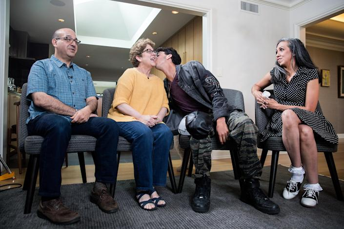 Michael Matt kisses his mother, Judy, while waiting to be interviewed on camera by reporter Lisa Belkin (out of frame) for Yahoo News, on June 23, 2018, in Providence, R.I. From left: Andrew Matt, Judy Matt, Michael Matt, Gina Aparicio. (Photo: Kayana Szymczak for Yahoo News)