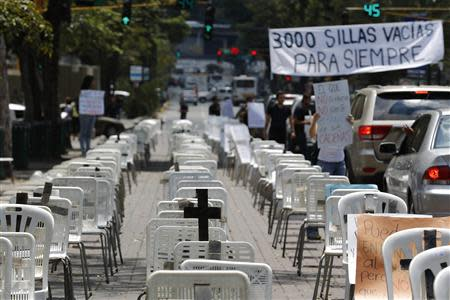 Anti-government protesters placed black crosses on white chairs, representing victims who died from violence, during a demonstration in Caracas March 15, 2014. REUTERS/Tomas Bravo